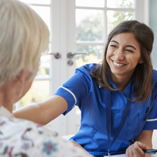 Young care nurse on home visit comforting senior woman